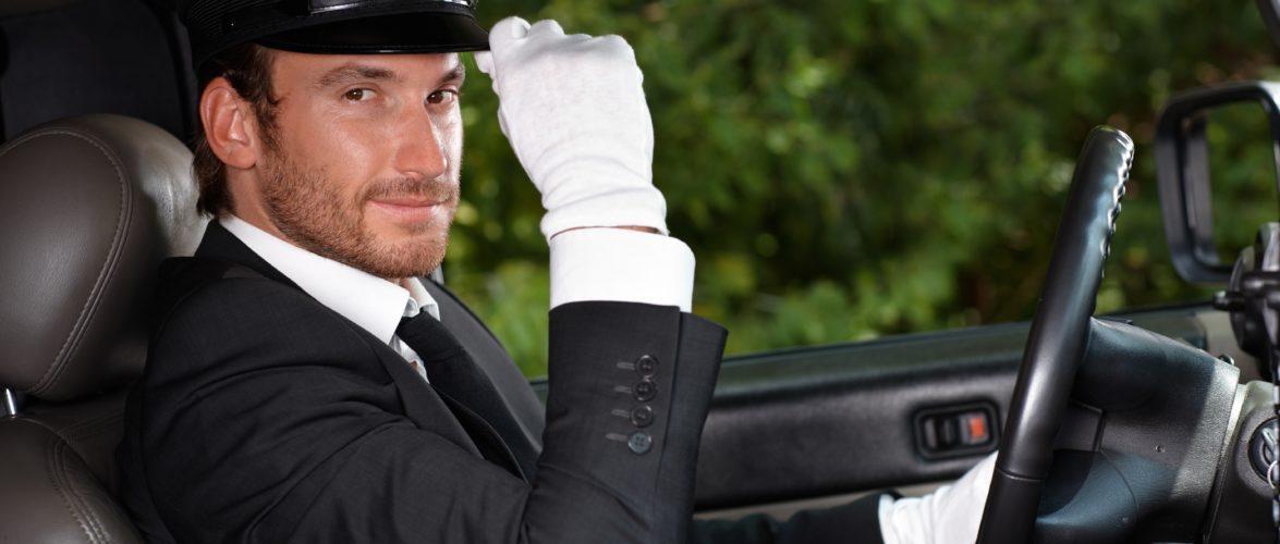 Confident chauffeur sitting in elegant automobile.