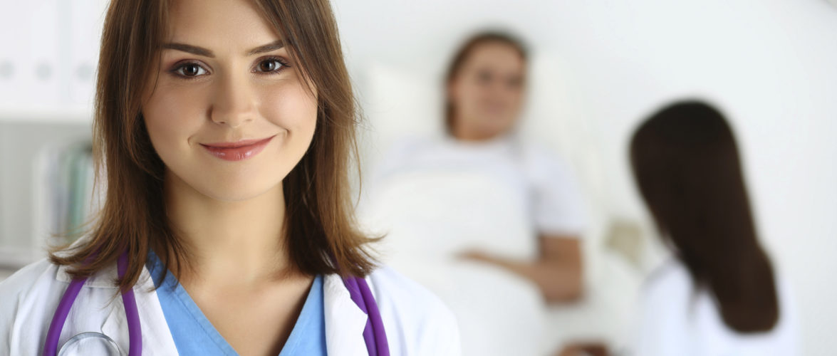 Beautiful female medicine doctor looking in camera in front of patient lying in bed and communicating with therapeutist. Physician or traumatologist medical concept. Medical care or insurance concept